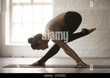 Young attractive woman in balance dancing pose, white loft studi - Stock Photo