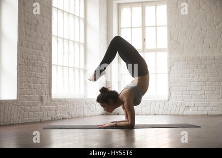 Young attractive woman in vrischikasana pose, white loft studio  - Stock Photo