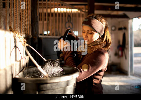 Sweden, Uppland, Faringso, Woman pouring water from watering can to bucket - Stock Photo