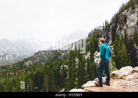 USA, Colorado, Rocky Mountain National Park, Man looking at mountains - Stock Photo