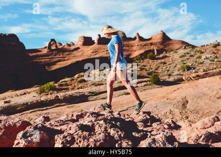 USA, Utah, Moab, Arches National Park, Woman walking on rocks - Stock Photo