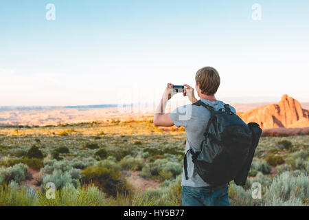 USA, Utah, Moab, Arches National Park, Man photographing landscape - Stock Photo