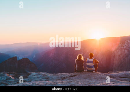 USA, California, Yosemite National Park, Taft Point, Man and woman watching sunset in mountains - Stock Photo