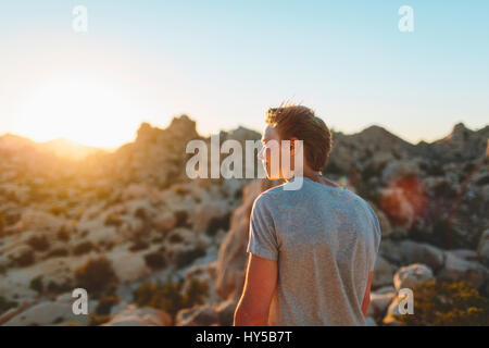 USA, California, Joshua Tree National Park, Young man contemplating at sunset - Stock Photo