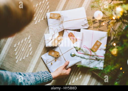 Finland, Man placing wrapped christmas gifts under tree - Stock Photo