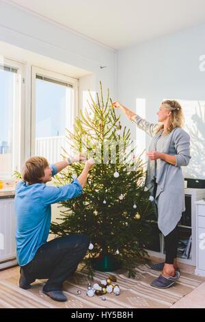 Finland, Helsinki, Couple decorating christmas tree together - Stock Photo