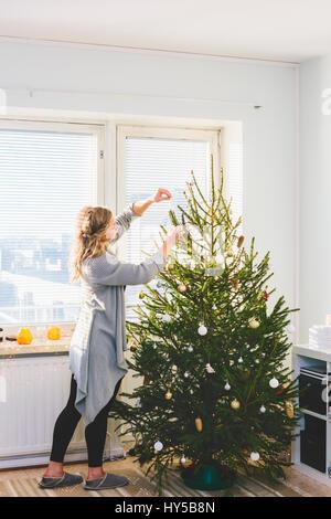 Finland, Helsinki, Woman decorating christmas tree - Stock Photo
