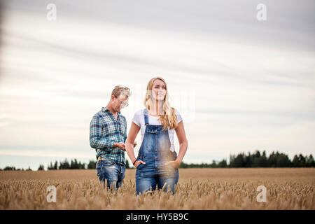 Finland, Uusimaa, Siuntio, Mid adult couple standing in wheat field - Stock Photo