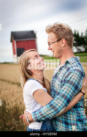 Finland, Uusimaa, Siuntio, Mid adult couple embracing in wheat field - Stock Photo