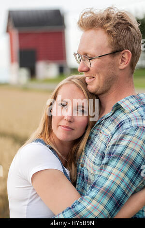 Finland, Uusimaa, Siuntio, Mid adult couple embracing in field - Stock Photo
