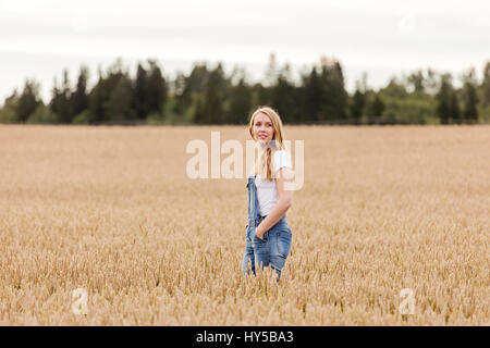 Finland, Uusimaa, Siuntio, Blonde woman standing in wheat field - Stock Photo