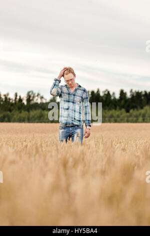 Finland, Uusimaa, Siuntio, Mid adult man standing in wheat field - Stock Photo