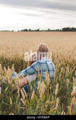 Finland, Uusimaa, Siuntio, Mid adult couple sitting in wheat field - Stock Photo
