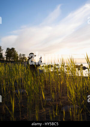 Finland, Ostrobothnia, Jakobstad, Faboda, Woman sitting among reeds by sea and photographing - Stock Photo