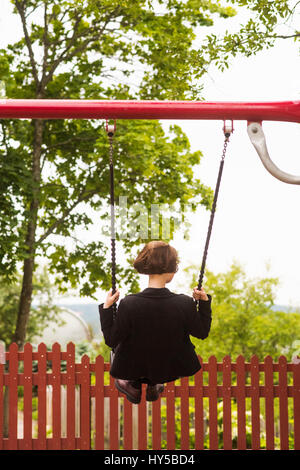 Finland, Pirkanmaa, Tampere, Young woman swinging in back yard - Stock Photo