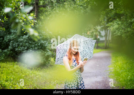 Finland, Pirkanmaa, Tampere, Woman wearing floral dress standing with umbrella in park - Stock Photo
