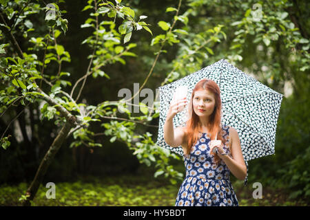 Finland, Pirkanmaa, Tampere, Woman wearing floral dress standing with umbrella in park and taking selfie - Stock Photo