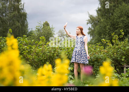 Finland, Pirkanmaa, Tampere, Woman taking selfie in rural scenery - Stock Photo