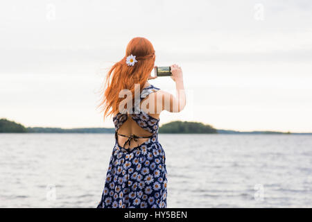 Finland, Pirkanmaa, Tampere, Woman photographing sea - Stock Photo