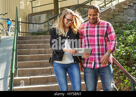 Sweden, Man and woman standing side by side in front of steps and looking at digital tablet - Stock Photo