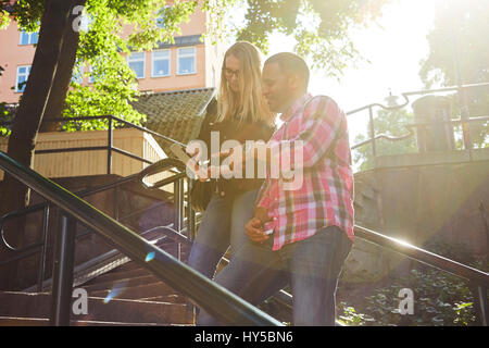 Sweden, Man and woman standing side by side looking at digital tablet in sunlight - Stock Photo