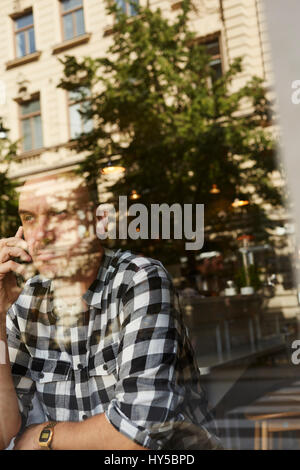 Sweden, Man sitting, talking on phone - Stock Photo