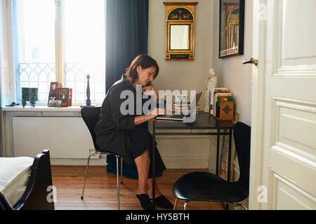 Sweden, Woman in black dress using laptop at home - Stock Photo