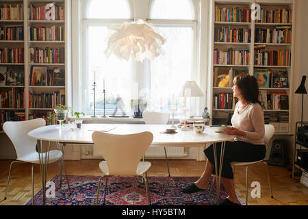 Sweden, Woman sitting alone at table - Stock Photo