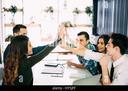 Photo editors giving high-five in meeting room at creative office room - Stock Photo