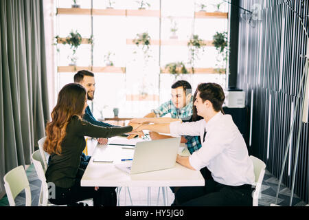 Businesspeople putting hands together on the table at the office meeting - Stock Photo
