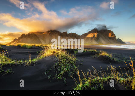 Sunset above  Vestrahorn (Batman Mountain) and its black sand beach in Iceland - Stock Photo