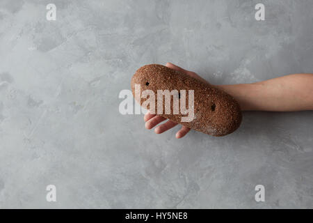 Loaf of bread in hand - Stock Photo