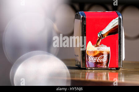 Coca Cola Napkin Holder on a cafe table in Madrid with highlights, shallow depth of field - Stock Photo