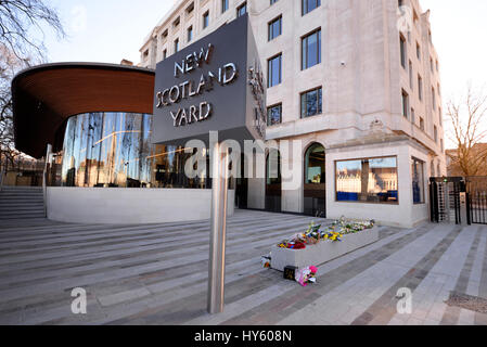 Floral tributes outside New Scotland Yard, London, following the terrorist action and death of PC Keith Palmer. - Stock Photo