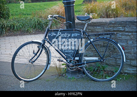 An old black bicycle chained to a lamp post and leaning against a stone wall. - Stock Photo