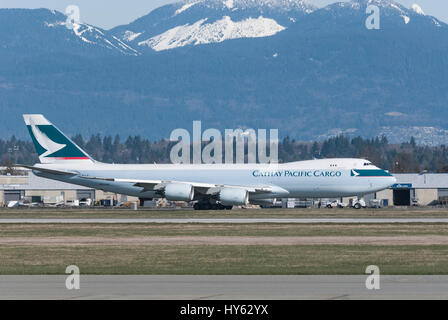Cathay Pacific Wide Body Boeing 747 cargo plane taxing down runway at Vancouver International airport. - Stock Photo