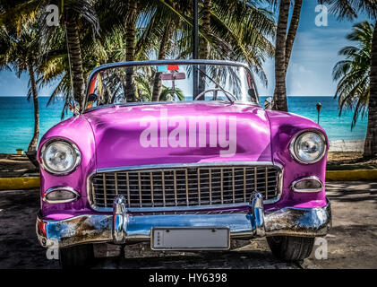 American beautiful pink convertible classic car parked on the beach in Varadero Cuba - Stock Photo