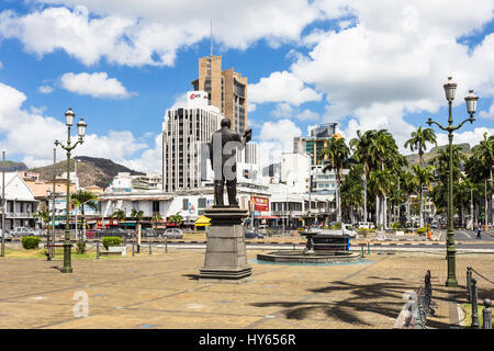 PORT LOUIS, MAURITIUS - NOVEMBER 18, 2016: A statue overlooks the waterfront promenade in front of the he modern - Stock Photo