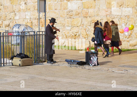 JERUSALEM, ISRAEL - DECEMBER 26, 2016:  A Jewish man in orthodox clothes plays the violin near the Jaffa gate to - Stock Photo