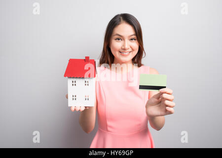 Invest in real estate concept. Woman holding small toy house and credit card in hands - Stock Photo