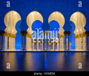 UNITED ARAB EMIRATES, ABU DHABI - CIRCA JANUARY 2017:  Pool, arches and columns of the Sheikh Zayed Mosque at night. - Stock Photo