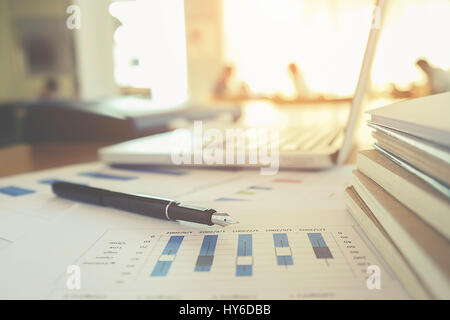 Business concept with copy space. Office desk table with pen focus and analysis chart, computer, notebook, cup of - Stock Photo