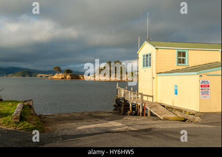 Boat houses at Otago Peninsula and Otago Harbour during sunset east of Dunedin, New Zealand