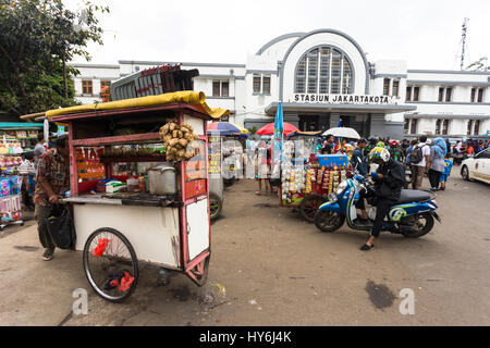 JAKARTA, INDONESIA - FEBRUARY 12, 2017: Street food vendors wait for customers in front of the Jakarta Kota train - Stock Photo