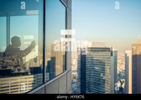 TOKYO  - JAPAN - JANUARY 11, 2017 A man is taking a photo of the view from the top of the Tokyo Metropolitan Government - Stock Photo