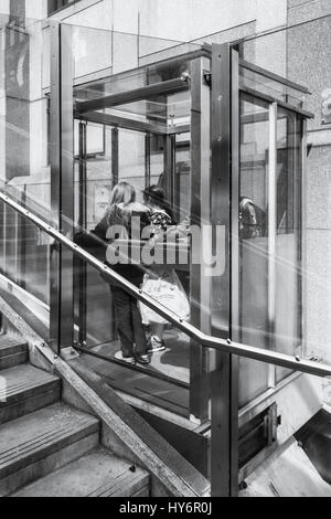 Black and white image of two girls in the funicular disabled access lift near St. Paul's, London, UK - Stock Photo