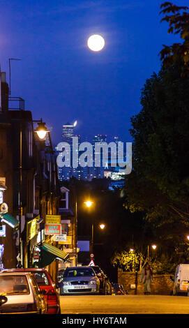 Night view over London, the full moon in a dark blue sky, Islington, UK - Stock Photo