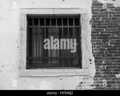 Old barred window on a distressed brick wall - Stock Photo