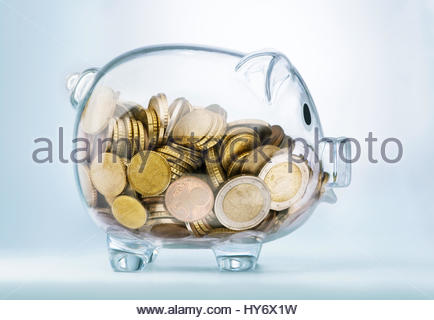 A see through piggy bank with money coins - Stock Photo