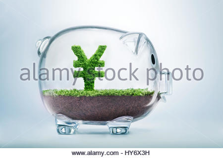 Piggy bank savings concept with grass growing in shape of Yuan sign - Stock Photo